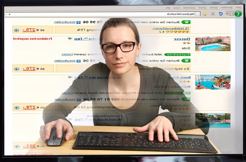 Young woman sitting at a computer surfing the Internet, booking a package tour with a hotel on a travel portal, view from within the computer, symbolic image : Stock Photo
