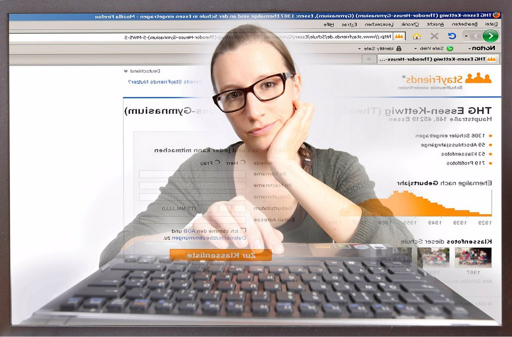 Young woman sitting at a computer surfing the Internet, viewing a page on Stayfriends.de, view from within the computer, symbolic image : Stock Photo
