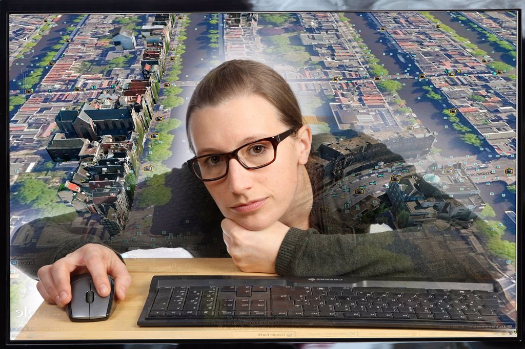 Stock Photo: 1848-608492 Young woman sitting at a computer using Google Street View, image detail with a section of the city of Amsterdam, people and license plate numbers have been censored, view from within the computer, symbolic image