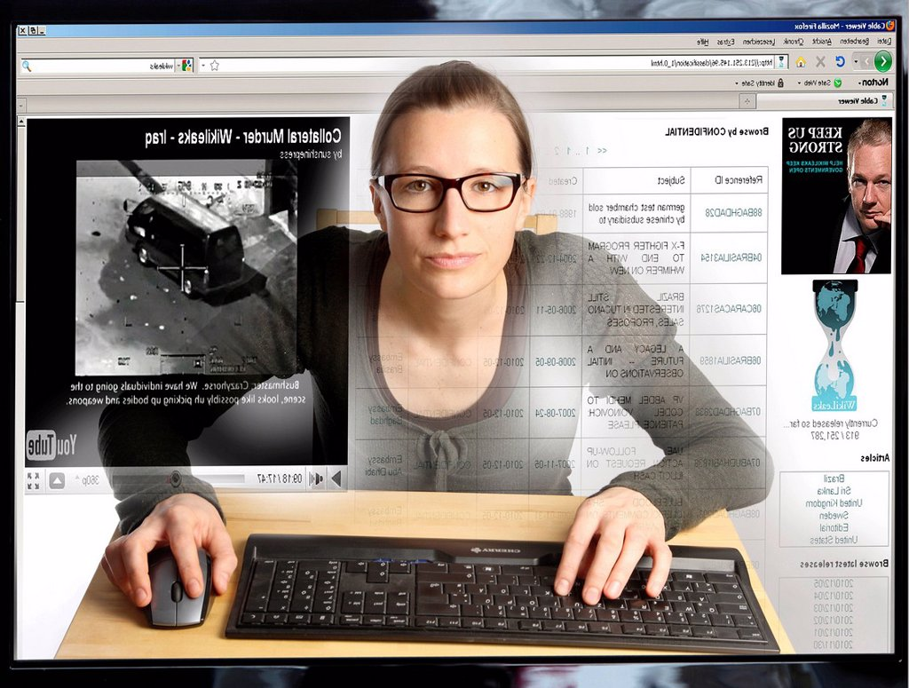 Young woman sitting at a computer surfing the Internet, viewing a page on the WikiLeaks site, view from within the computer, symbolic image : Stock Photo