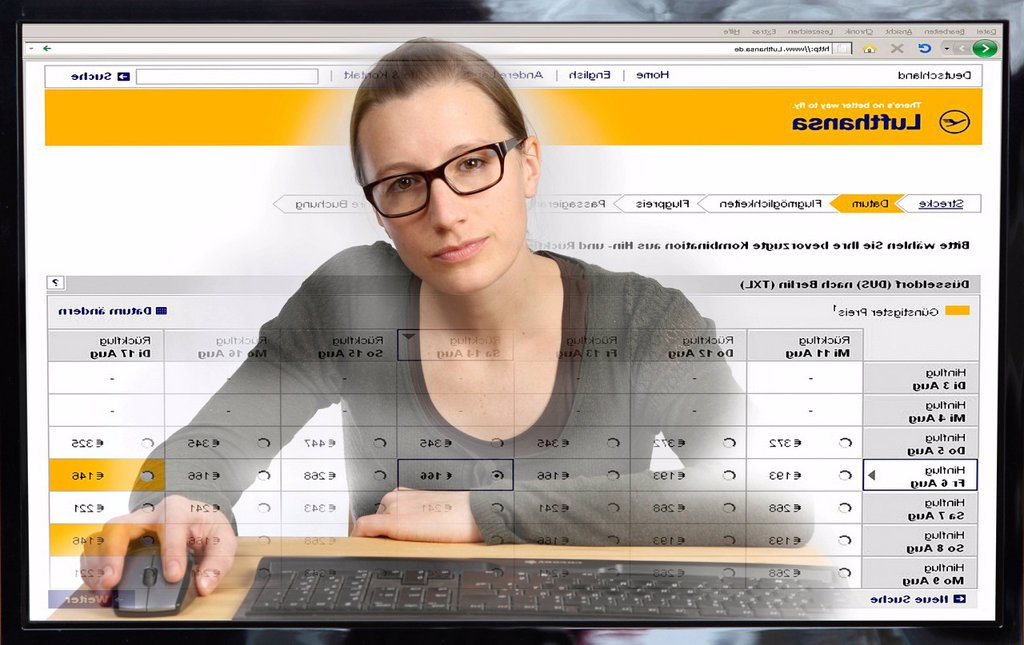 Young woman sitting at a computer surfing the Internet, booking a flight on the Lufthansa site, view from within the computer, symbolic image : Stock Photo
