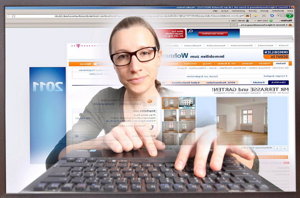 Young woman sitting at a computer surfing the Internet, viewing a real estate site, Immobilienscout24.de, view from within the computer, symbolic image : Stock Photo