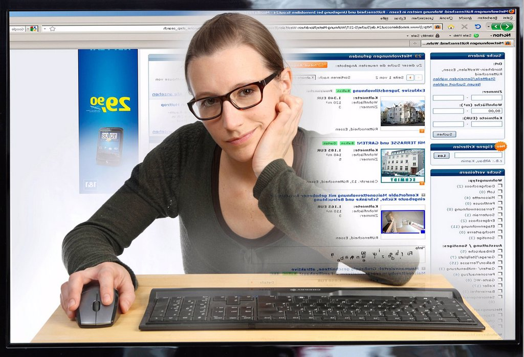 Stock Photo: 1848-609110 Young woman sitting at a computer surfing the Internet, viewing a real estate site, Immobilienscout24.de, view from within the computer, symbolic image