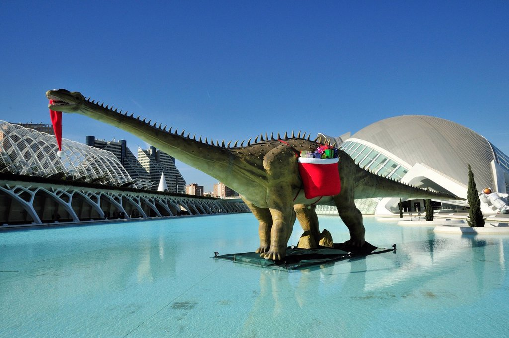 Stock Photo: 1848-609621 Dinosaur bearing Christmas presents standing in front of L´Hemisferic, Imax cinema and planetarium, Ciudad de las Artes y las Ciencias, City of Arts and Sciences, designed by Spanish architect Santiago Calatrava, Valencia, Comunidad Valenciana, Spain, Eur. Dinosaur bearing Christmas presents standing in front of L´Hemisferic, Imax cinema and planetarium, Ciudad de las Artes y las Ciencias, City of Arts and Sciences, designed by Spanish architect Santiago Calatrava, Valencia, Comunidad Valenciana