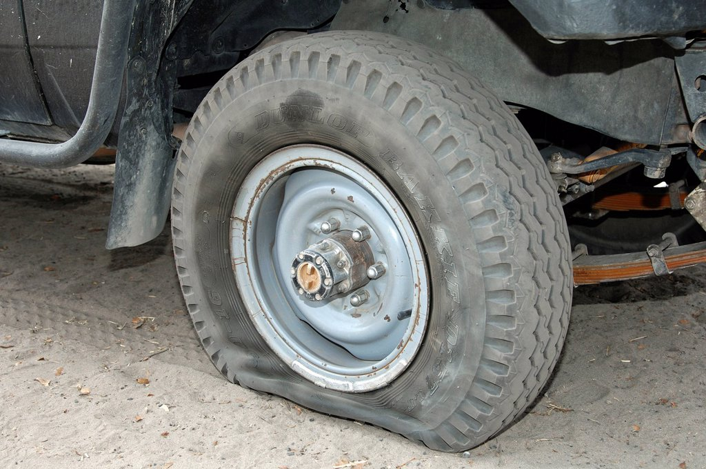Stock Photo: 1848-610387 Flat Dunlop tyre on a jeep, Moremi Nature Reserve, Botswana, Africa
