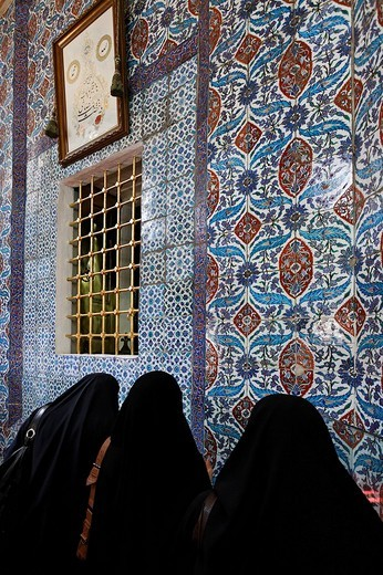 Three black veiled Muslim women, Carsaf, pray in front of the grave of Muhammad´s standard_bearer Eyuep Ensari, Eyuep village, Golden Horn, Istanbul, Turkey : Stock Photo