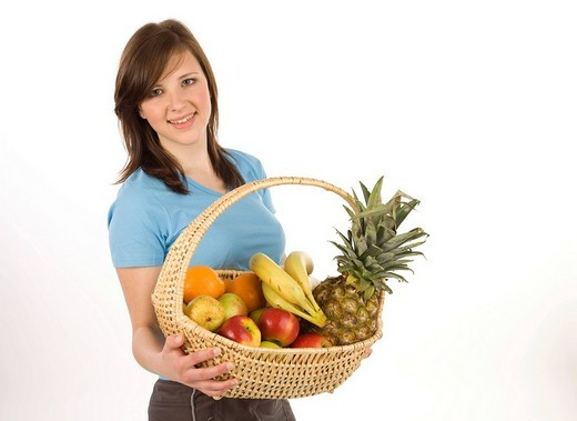 Young woman with fruit basket, smiling : Stock Photo