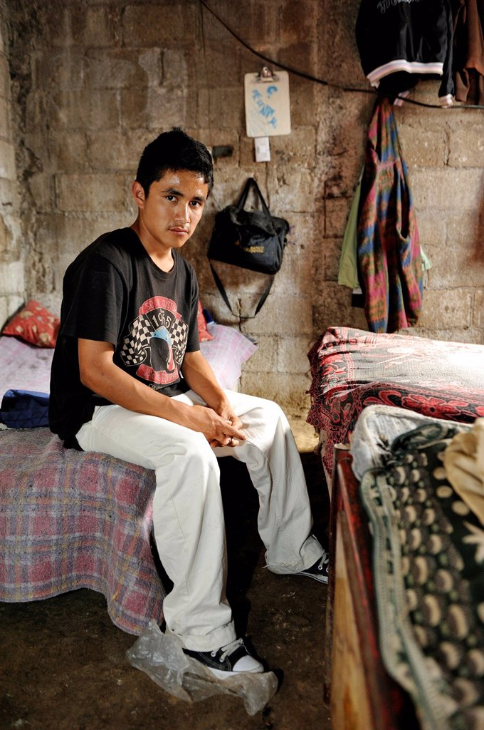 Stock Photo: 1848-613111 Teenager, 16 years old, sitting on his bed in a humble hut, Lomas de Santa Faz slum, Guatemala City, Guatemala, Central America