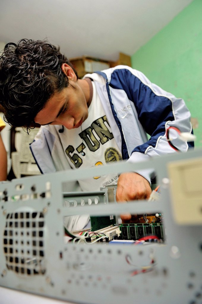Teenager, 18 years old, a former hired killer and member of a gang of youths, Mara, learning how to build a working computer from used parts at the Parque Technologico Ceiba vocational school, Zona 1, Guatemala City, Guatemala, Central America : Stock Photo