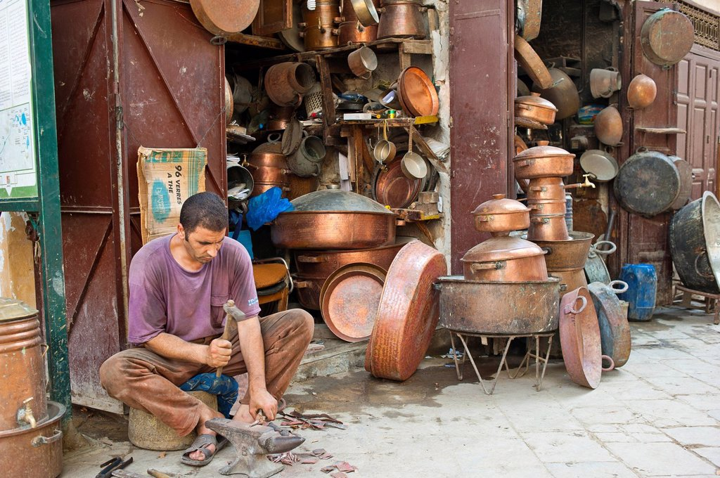 A coppersmith at work outside his shop in the coppersmiths´ alley, souk, bazaar, Medina, Fes, Morocco, Africa : Stock Photo