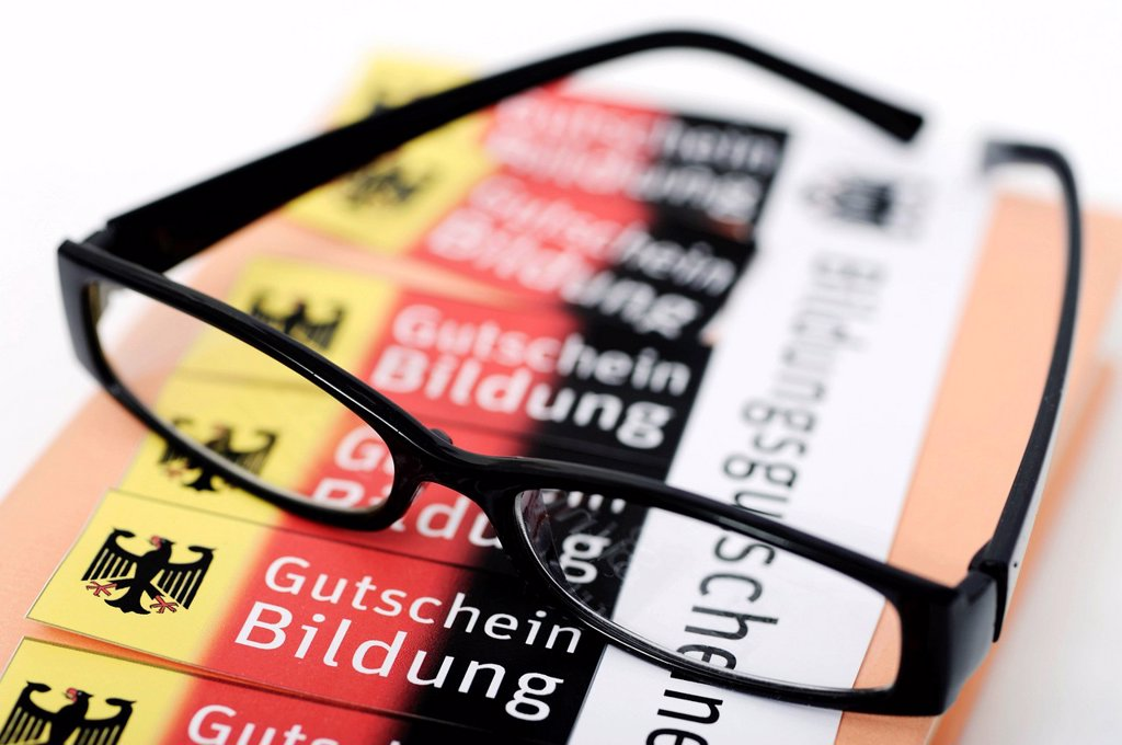 Stock Photo: 1848-613486 Glasses lying on vouchers, Bildungsgutschein coupons, lettering Gutschein Bildung, German for education voucher, symbolic image