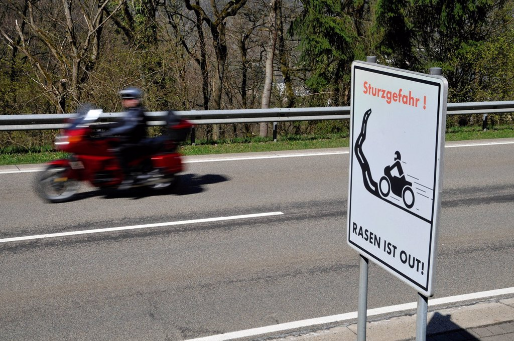 Stock Photo: 1848-613652 Motorcyclist on a country road with a warning sign, Sturzgefahr _ Rasen ist out, German for dangerous curves _ no speeding, Eifel, Germany, Europe