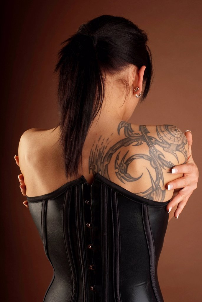 Woman, dressed in a Gothic style, wearing a latex corset, seen from behind with a tattoo : Stock Photo