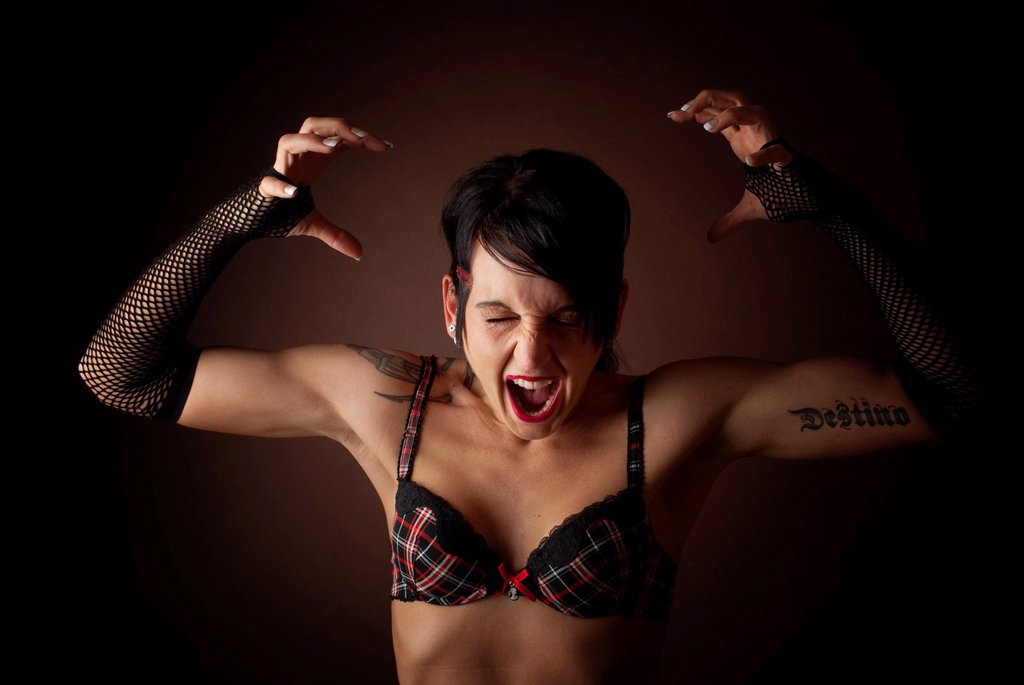 Woman, dressed in a Gothic style, wearing a bra and screaming : Stock Photo