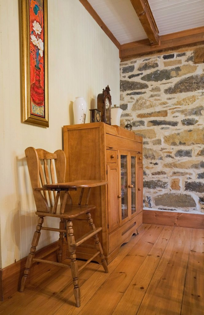Stock Photo: 1848-615428 High chair and small dresser in the dining room of an old Canadiana cottage_style residential fieldstone home, circa 1832, Laurentians, Quebec, Canada. This image is property released for book, calendar, magazine, newspaper and editorial use only. LUPR017. High chair and small dresser in the dining room of an old Canadiana cottage_style residential fieldstone home, circa 1832, Laurentians, Quebec, Canada. This image is property released for book, calendar, magazine, newspaper and editorial use o