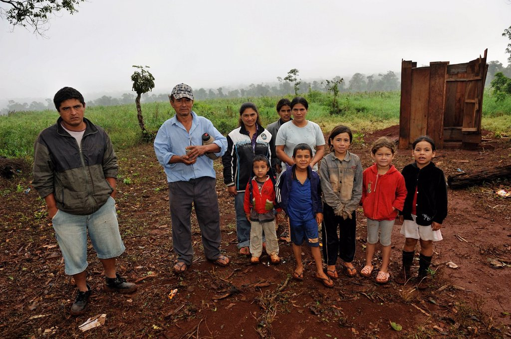 Land grabbing, a smallholder´s family, they were forced off their land by investors and now live in makeshift huts by the roadside, the soybean field of the landowner at back which used to be their own plot, Carlos Antonio Lopez district, Itapua province,. Land grabbing, a smallholder´s family, they were forced off their land by investors and now live in makeshift huts by the roadside, the soybean field of the landowner at back which used to be their own plot, Carlos Antonio Lopez district, Itap : Stock Photo