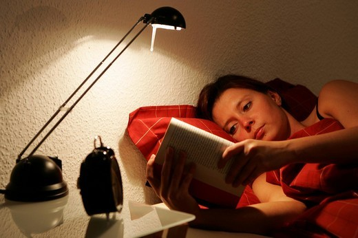Young woman is reading a book in her bed, late in the evening : Stock Photo