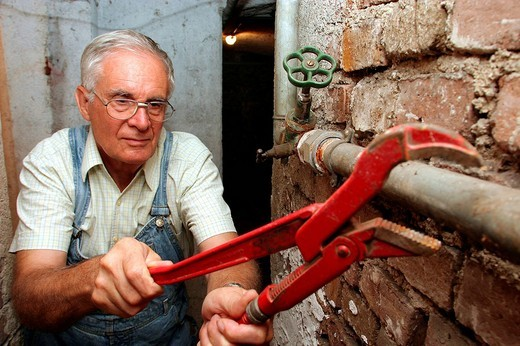 Plumber fixes a burst pipe : Stock Photo