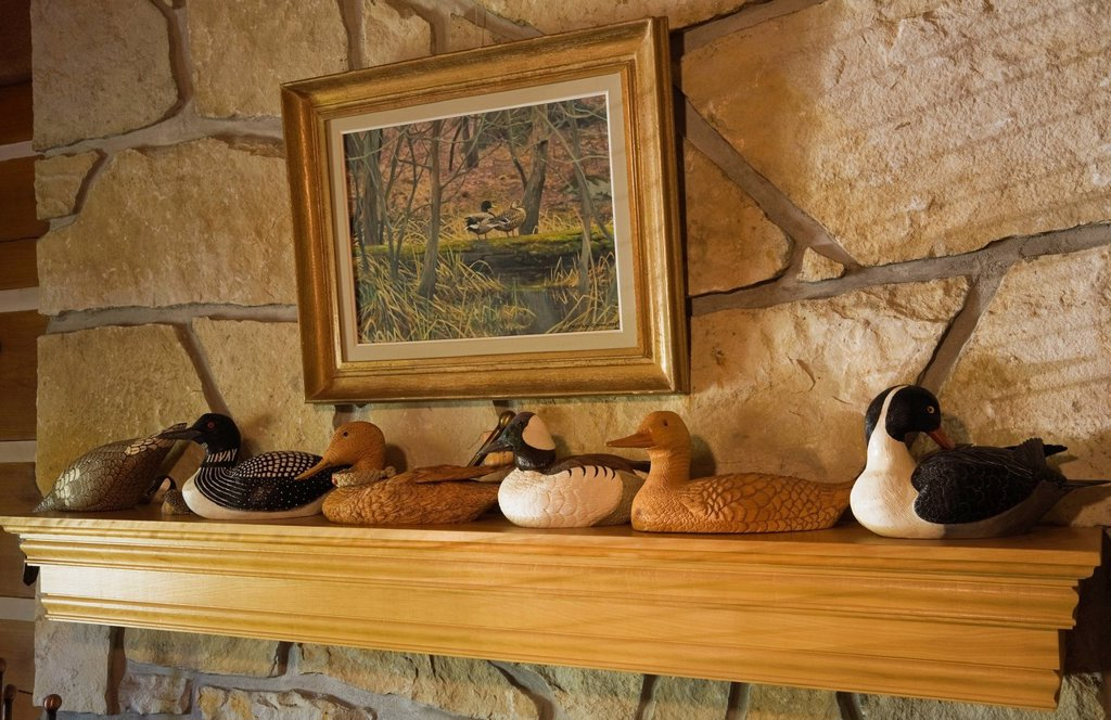 Stock Photo: 1848-617413 Wooden duck and loon carvings on a fireplace mantle in the living room of a 1977 reproduction of an old Canadiana cottage_style residential log home, Quebec, Canada. This image is property released for book, calendar, magazine, newspaper and editorial use. Wooden duck and loon carvings on a fireplace mantle in the living room of a 1977 reproduction of an old Canadiana cottage_style residential log home, Quebec, Canada. This image is property released for book, calendar, magazine, newspaper and e