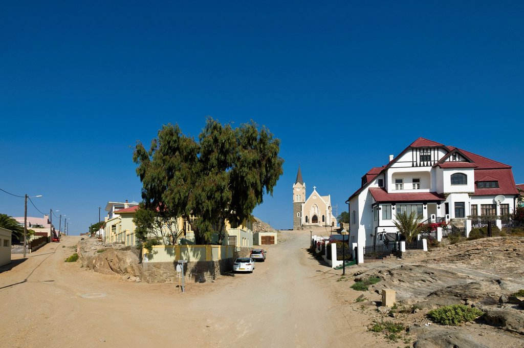 House with half timbered elements and the rock church, Kirchstrasse street, Luederitz, Namibia, Africa : Stock Photo