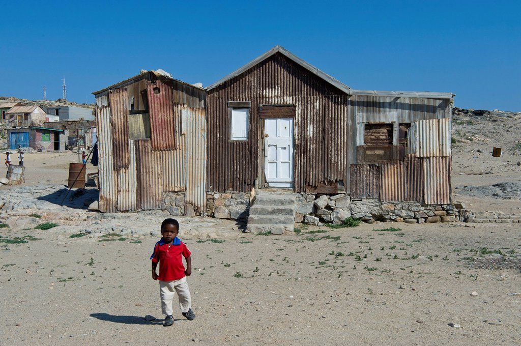 Stock Photo: 1848-618171 Child standing in front of an old corrugated iron house, outskirts of Luederitz, Namibia, Africa