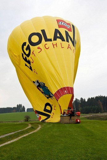 Landing of a hot_air balloon and letting out of the hot air, Oberallgaeu, Germany : Stock Photo