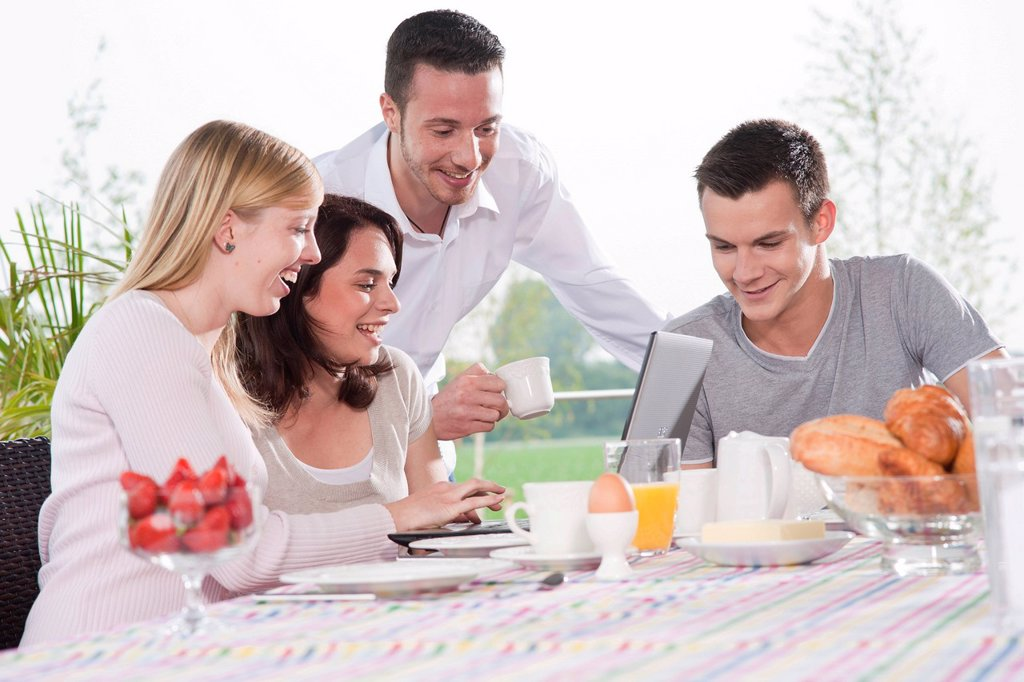 Stock Photo: 1848-618775 Young people using a laptop while having breakfast on a terrace