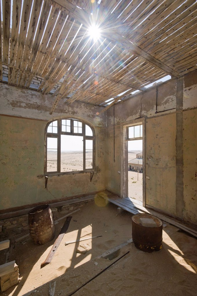 Sun shining through the ceiling of a ruined house, abandoned diamond mine, Kolmanskop, Namibia, Africa : Stock Photo