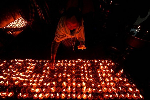 An elderly woman lights Tibetan butterlamps in Bodnath, a northeastern suburb of Kathmandu, Nepal, Asia : Stock Photo