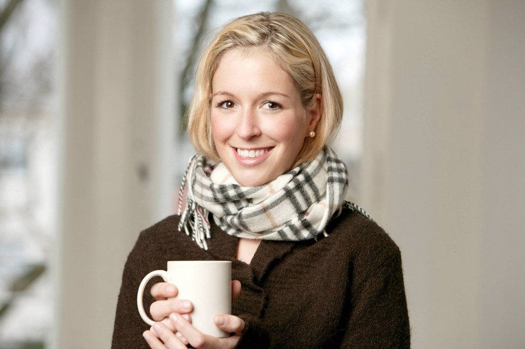 Smiling young blonde woman in a dark sweater and wool scarf holding a mug : Stock Photo