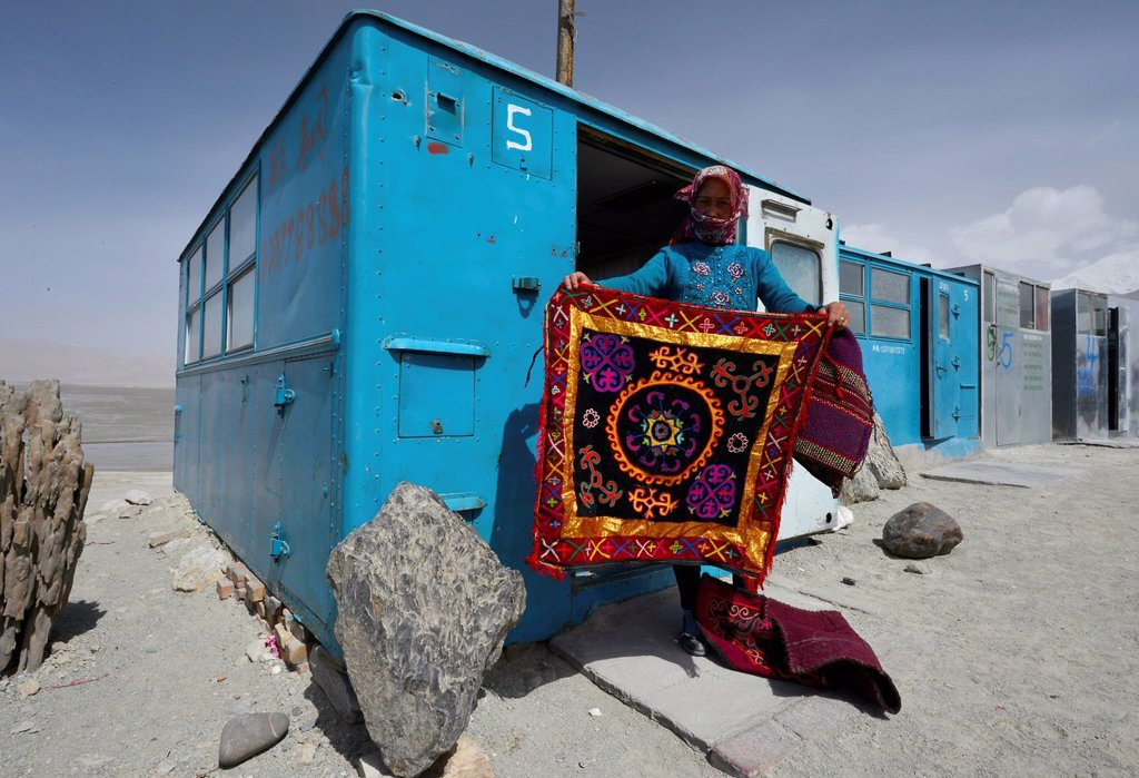 Stock Photo: 1848-621201 Kazakh woman showing a hand_woven, embroidered wall carpet, simple blue containers, house boxes, storage containers, shops of the Kazakhs in the Kongur Mountains, Silk Road, Pamir, Xinjiang, China, Asia
