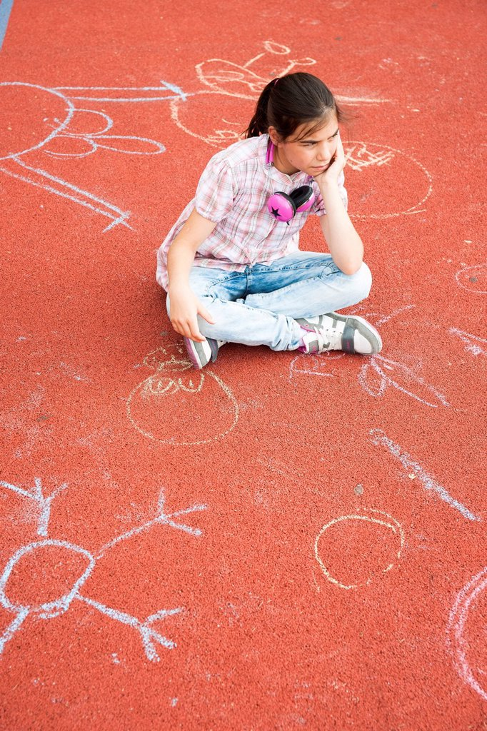 Stock Photo: 1848-622928 Girl sitting around bored on the school playground