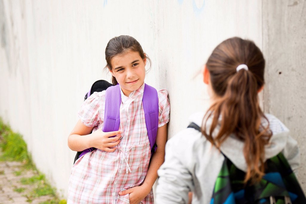 Stock Photo: 1848-624054 Two girls talking to each other on their way to school