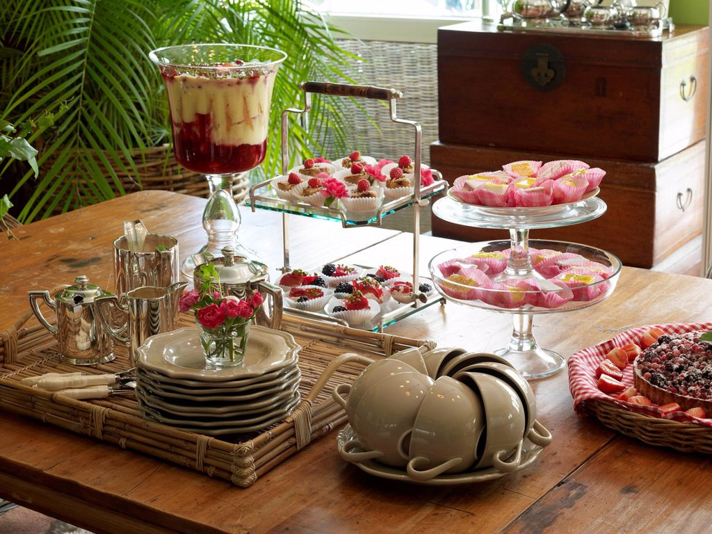 Stylish decorated coffee table in a romantic setting with fruit pudding, trifle, and petit fours : Stock Photo