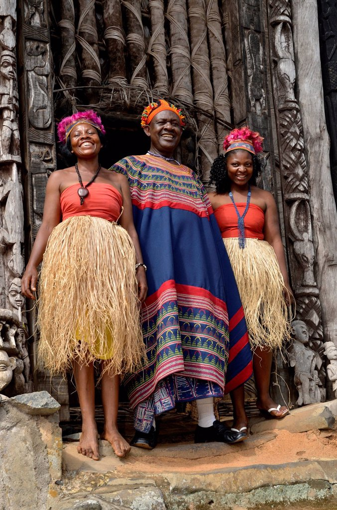 King Fon Abumbi II, head of one of the traditional kingdoms in north west Cameroon, in front of the Achum sanctuary at his seat of power with two of his favourite wives, Bafut Palace, near Bamenda, Cameroon, Central Africa, Africa : Stock Photo