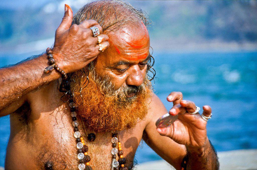 Stock Photo: 1848-626057 Sadhu, holy man, doing his washing and praying ceremony in the morning at the holy Narmada river, Omkareshwar, India, Asia