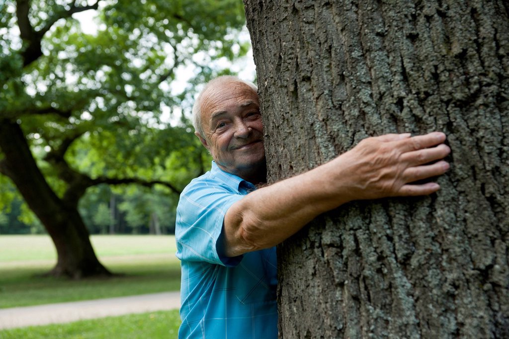 Stock Photo: 1848-626355 Elderly man hugging a tree, in a good mood