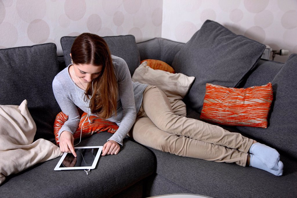 Stock Photo: 1848-626490 Girl playing at home with an iPad, tablet computer, wireless internet access