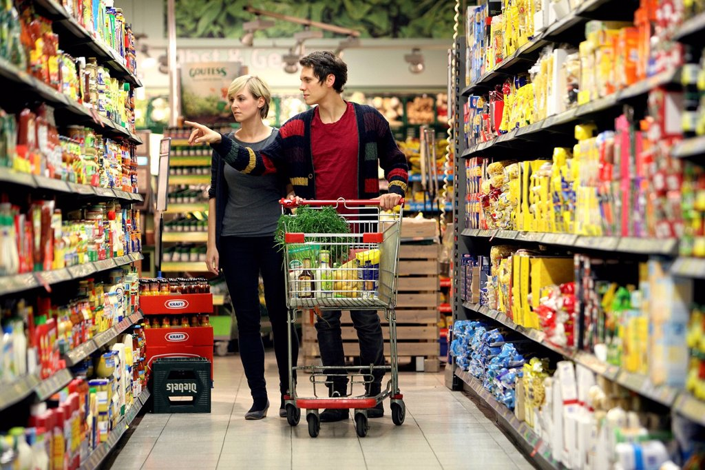Stock Photo: 1848-626528 Young couple grocery shopping at the supermarket, shelves with various products, food hall, supermarket, Germany, Europe