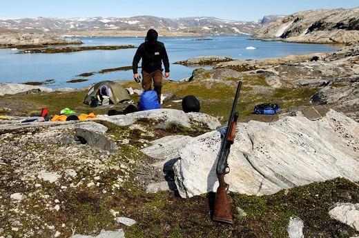 Trekker checking his shotgun for defence against polar bears, Ikasartivaq Fiord, East Greenland : Stock Photo