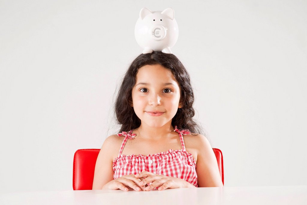 Girl with a piggy bank on her head : Stock Photo