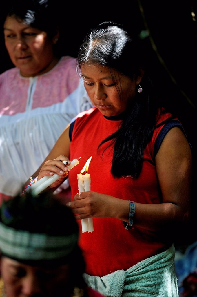 Stock Photo: 1848-627308 Young woman lighting candles at traditional ablutions to ward off evil spirits and to cleanse the soul of the indigenous Caranqui people, this ceremony starts the celebrations of the sun festival of Inti Raymi, Torres Jucho, Paroquia La Esperanza, Canton. Young woman lighting candles at traditional ablutions to ward off evil spirits and to cleanse the soul of the indigenous Caranqui people, this ceremony starts the celebrations of the sun festival of Inti Raymi, Torres Jucho, Paroquia La Esperan