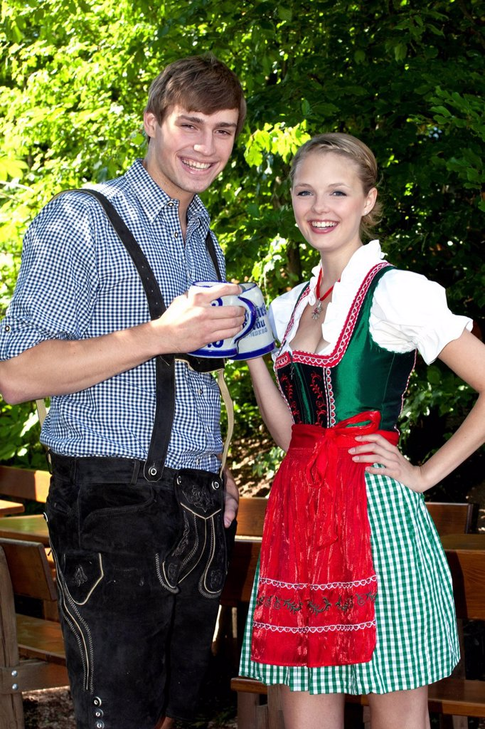 Young couple in dirndl and lederhosen standing in the beer garden, at Pettstatt, Upper Franconia, Bavaria, Germany, Europe : Stock Photo