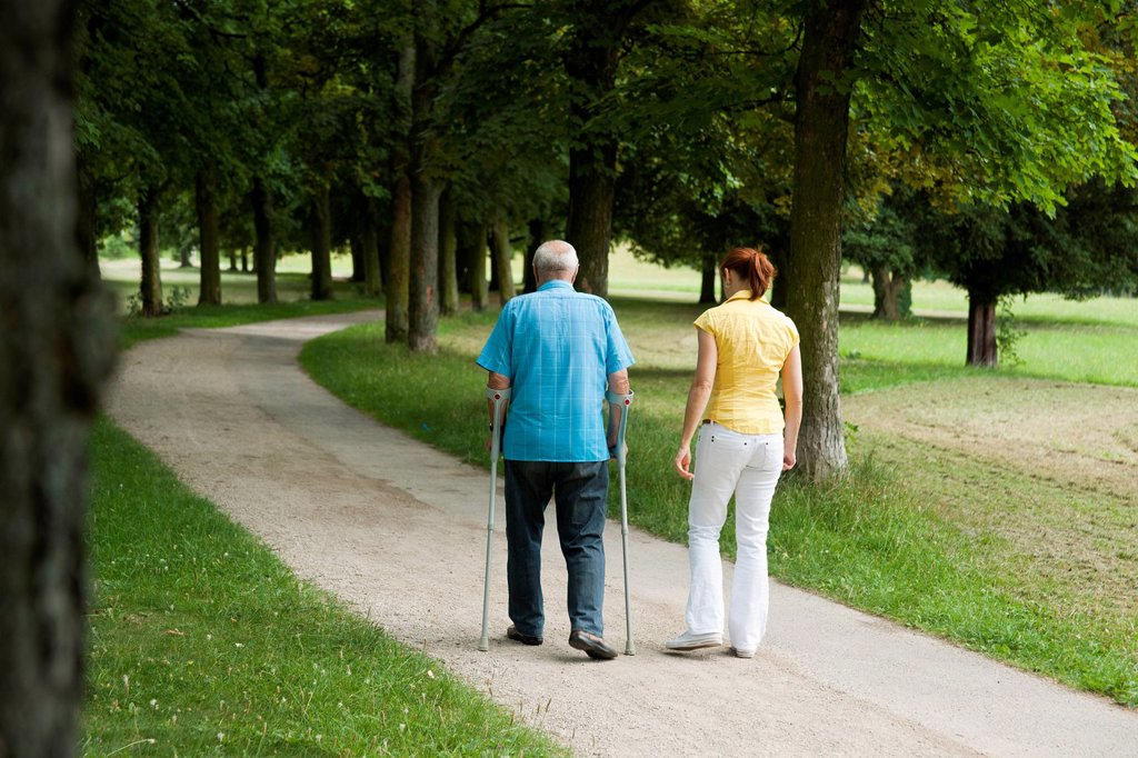 Stock Photo: 1848-627825 Woman and an elderly man on crutches strolling in the park