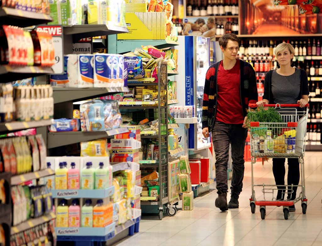Young couple grocery shopping at the supermarket, shelves with various products, food hall, supermarket, Germany, Europe : Stock Photo