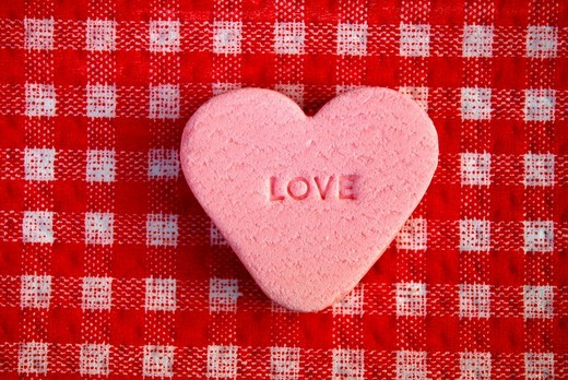 Stock Photo: 1848-62823 Single pink heart_shaped grape sugar candy with stamped in Love lettering on a red chequered tablecloth