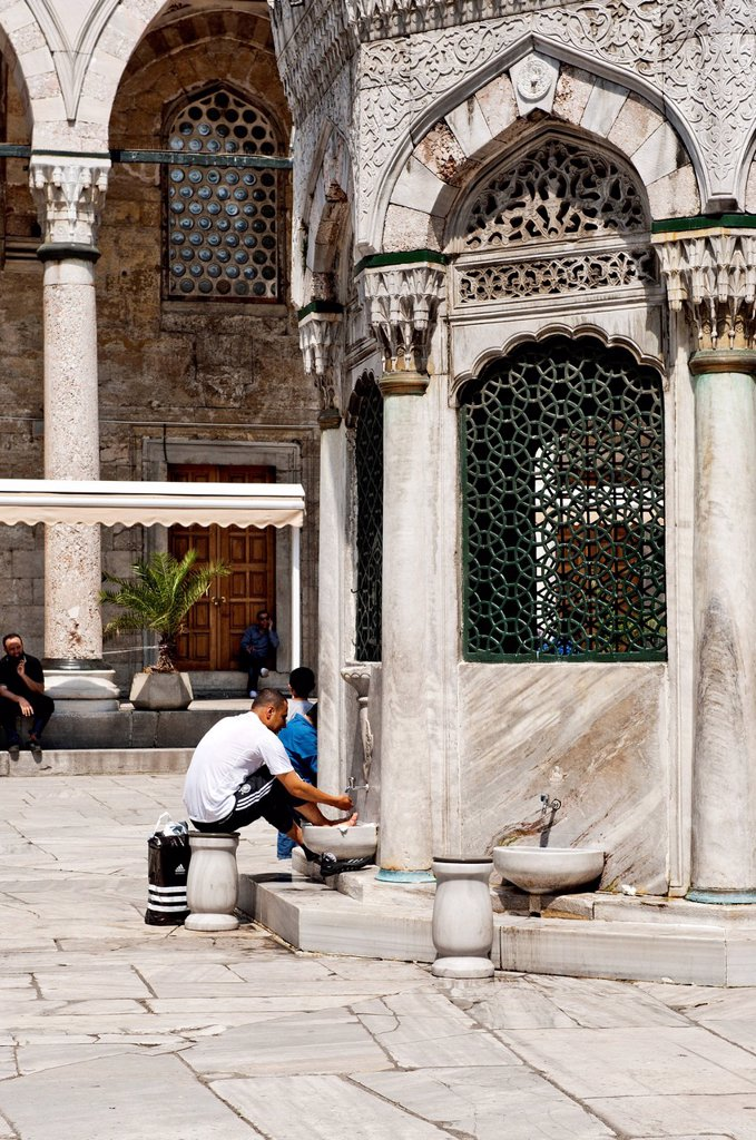 Stock Photo: 1848-628608 Man washing his feet in the washhouse in the courtyard of the New Mosque, Yeni Cami, Istanbul, Turkey