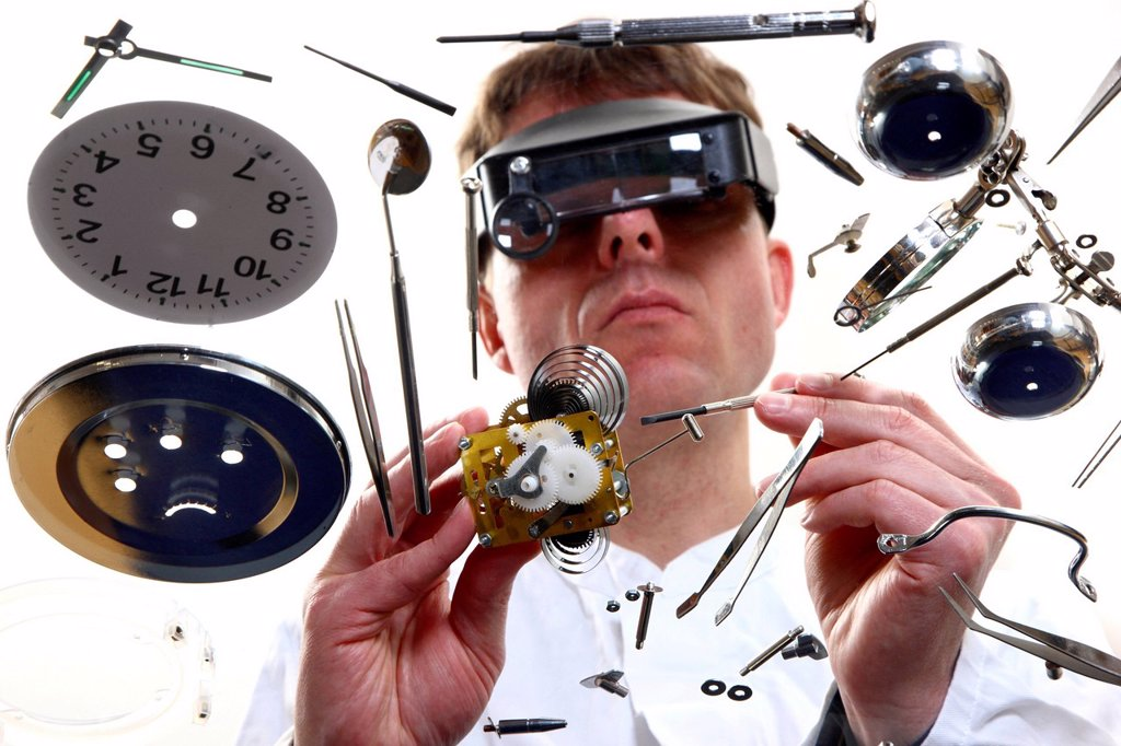 Stock Photo: 1848-628708 Precision mechanics, watchmaker repairing a clockwork, alarm clock, using a head_worn loupe system