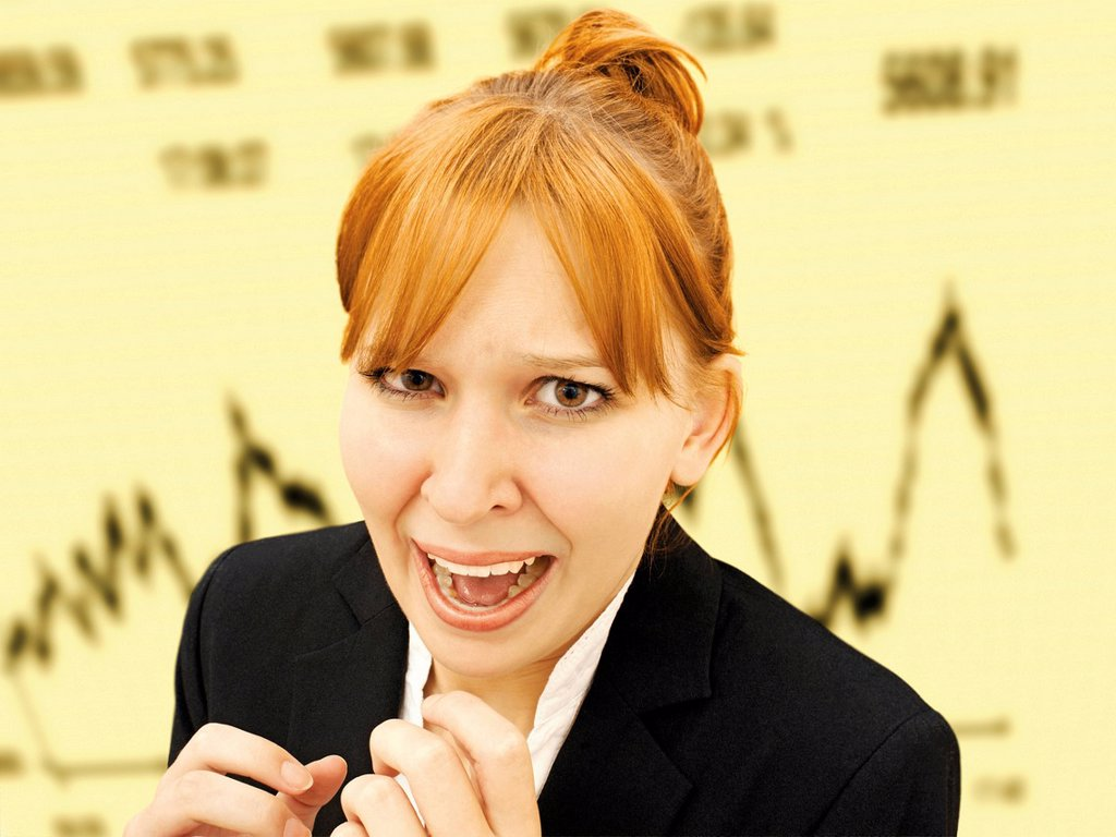 Portrait of an excited, hysterical businesswoman standing in front of a stock market index : Stock Photo