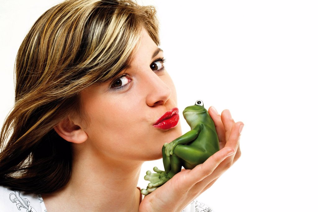 Stock Photo: 1848-630280 Young woman kissing a green frog in her hand